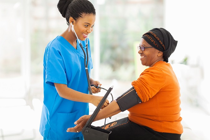 Nurse checking senior woman's blood pressure