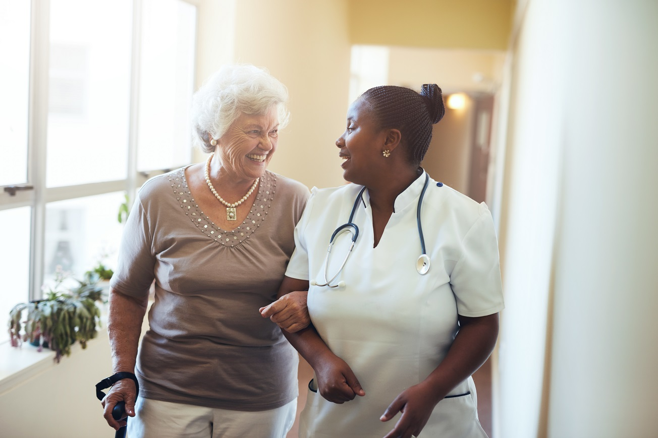 Nurse walking with patient and smiling