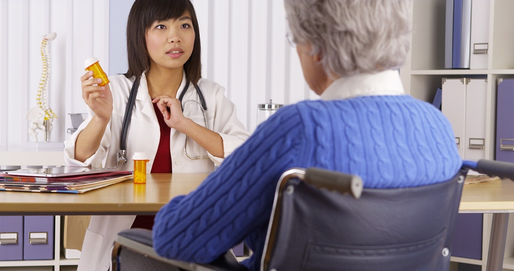 Asian doctor talking about medication to elderly patient