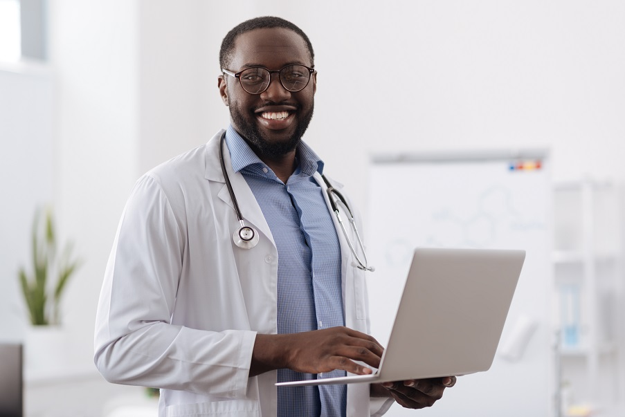 Doctor standing with laptop
