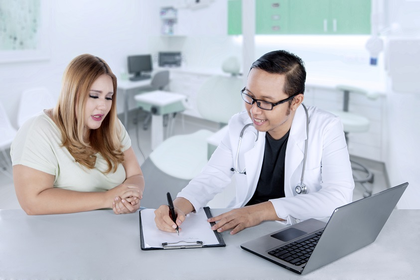 Doctor talking to patient and writing down notes