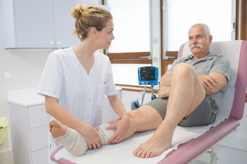 Nurse bandaging leg of senior patient
